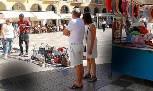 Los artesanos conviven con los vendedores ilegales en la Plaça Major de Palma.