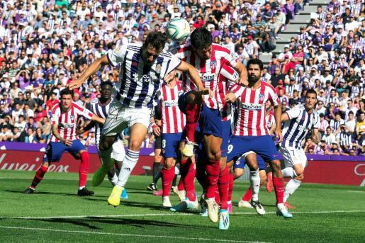 El jugador del Atlético de Madrid Stefan Savic, disputa el balón con el futbolista del Real Valladolid Kiko Olivas.