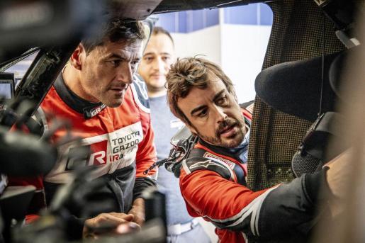 Fernando Alonso y Marc Coma observan su vehículo.