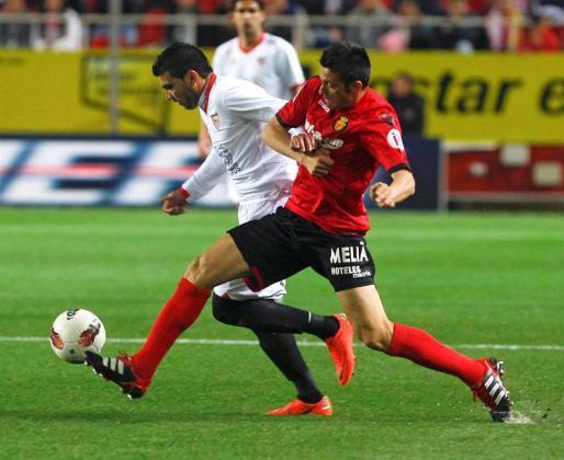 El jugador del Sevilla José Antonio Reyes (i) trata de escapar del israelí Tomer Hemed (d), del Mallorca, durante el partido de Liga que están disputando esta noche en el estadio Sánchez Pizjuán.