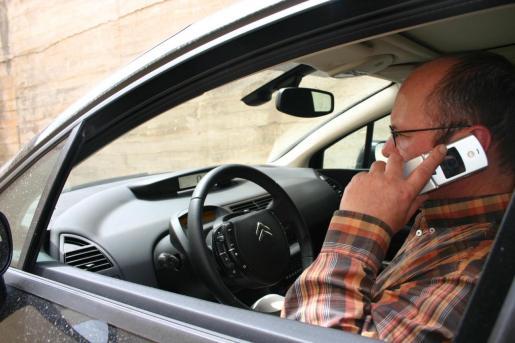 Un conductor utiliza su teléfono móvil.