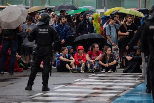 Un grupo de manifestantes, sentados en el Aeropuerto de Barcelona-El Prat.