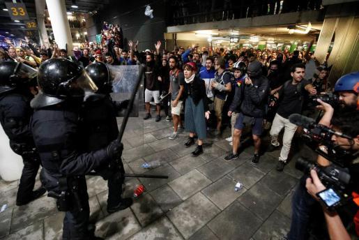 Manifestantes ante la policía en El Prat.