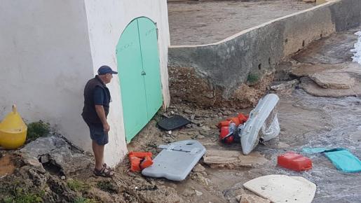 Un vecino de la zona observa los objetos arrastrados por el mar en el Port d'Andratx.