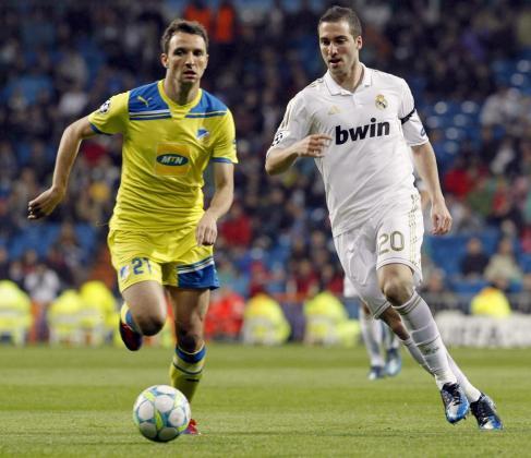 El delantero argentino del Real Madrid, Gonzalo Higuaín (d) pelea un balón con el centrocampista brasileño del Apoel Nicosia, Gustavo Manduca.