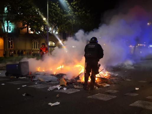 Un mosso d'Esquadra intenta apagar una hoguera durante los disturbios posteriores a las concentraciones convocadas por los CDR en Barcelona contra la sentencia del proceso independentista.