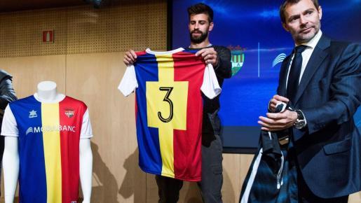 Gerard Piqué (izquierda) observa la camiseta del FC Andorra durante su presentación.