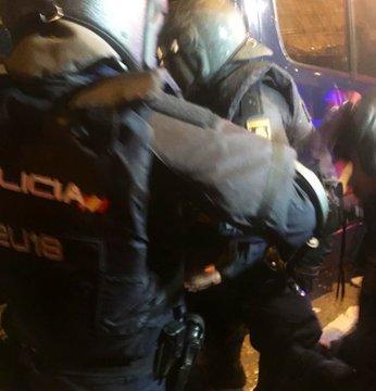 Compañeros del policía herido lo trasladan al furgón para llevarlo al hospital.