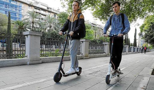 Dos jóvenes circulando en patinete eléctrico por el Paseo Mallorca.