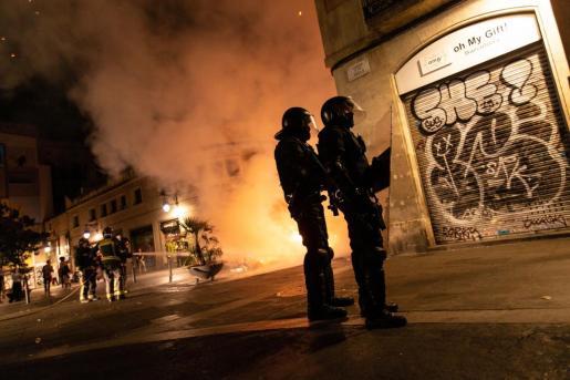 Mossos d'esquadra controlan una calle de el raval mientras los bomberos apagan una barricada de fuego durante una nueva protesta convocada por los autodenominados Comités de Defensa de la República (CDR).