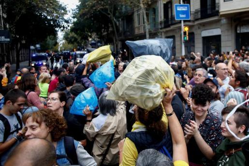 Centenares de personas han arrojado bolsas de basura, en su mayoría rellenas de papel, en el perímetro de seguridad de la sede en Barcelona de Delegación del Gobierno.