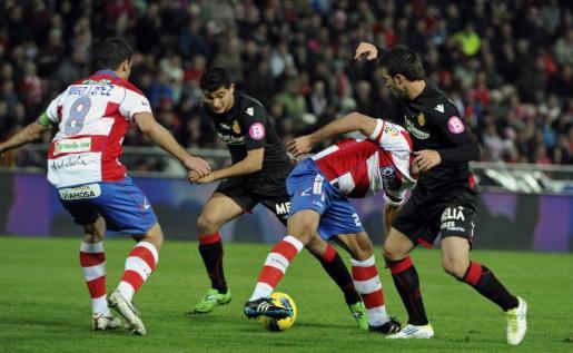 El jugador del Granada, Moises (2d), intenta controla el balón ante los jugadores del Real Mallorca, durante el encuentro correspondiente a la decimotercera jornada de primera división, que ambos equipos disputaron en el estadio granadino de Los Cármenes.