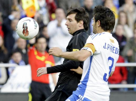 El delantero argentino del FC Barcelona Lionel Messi (i) pugna por el balón con el defensa del Real Zaragoza Javier Paredes.