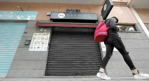 Un joven pasa por delante de la barrera del restaurante Ca's Músic de Palma.