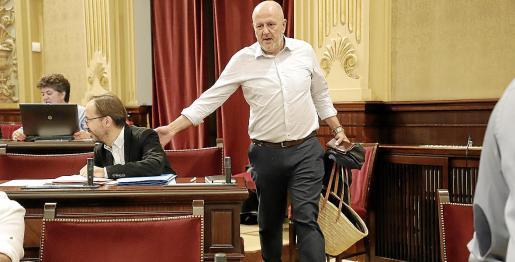 El portavoz parlamentario de Més per Mallorca, Miquel Ensenyat, a su llegada al pleno, saludando con un gesto en la espalda a Josep Castells, de Més per Menorca.