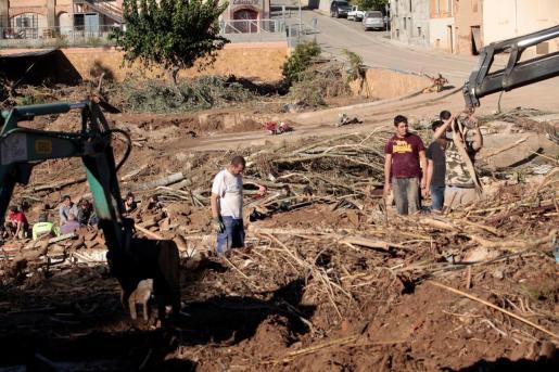 Vecinos realizan tareas de limpieza en la población de L'Espluga de Francolí (Tarragona) muy afectada por las riadas de esta semana, mientras los equipos de rescate ha intensificado este viernes la búsqueda de los 4 desaparecidos en las riadas.