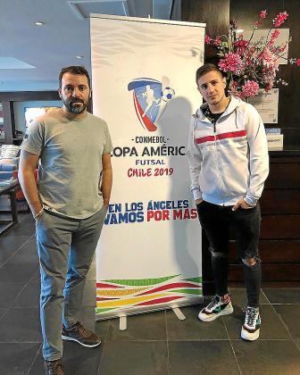 José Tirado y Nico Sarmiento posan junto al cartel de la Copa América suspendida por los disturbios en Chile.