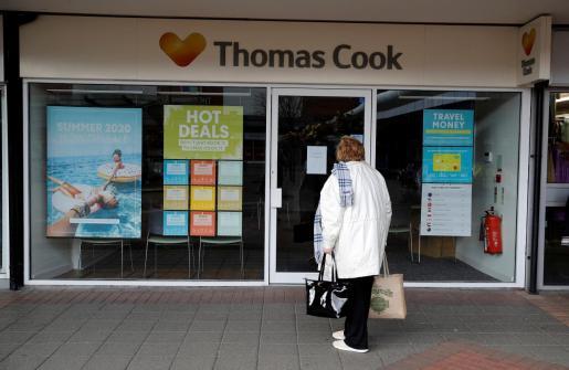Una mujer ante una agencia de viajes de Thomas Cook.