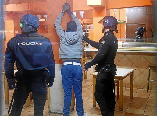 Agentes de la Policía Nacional detienen a un inmigrante en una operación.