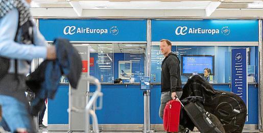Varios viajeros pasan este lunes ante las oficinas de Air Europa en la terminal de salidas del aeropuerto de Palma.