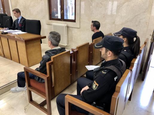 Los acusados, custodiados por dos policías nacionales, ayer en la Audiencia de Palma.