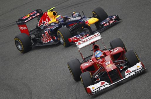 El piloto español del equipo Ferrari de Fórmula 1 Fernando Alonso conduce su monoplaza por delante del australiano Mark Webber, del equipo Red Bull.
