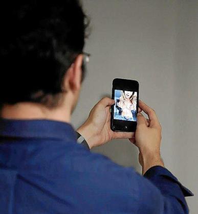 Un joven mira un vídeo porno en su móvil.