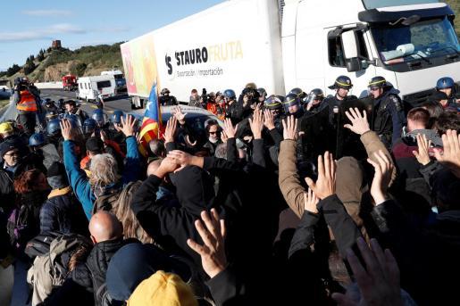 Gendarmes franceses tratan de desbloquear el corte de la autopista que enlaza España y Francia en el paso de Le Perthus.