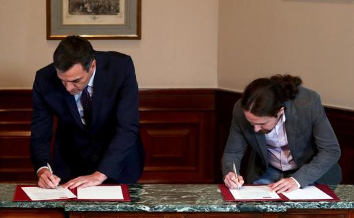Pedro Sánchez y Pablo Iglesias firman el preacuerdo de gobierno.