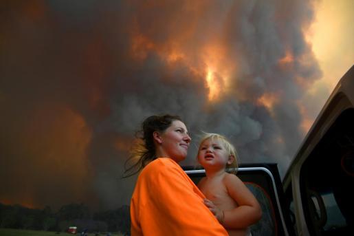 Una mujer con su hija escapando de uno de los incendios que asolan Australia.