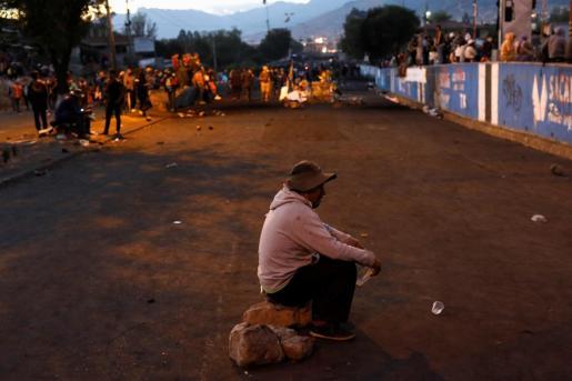 Un hombre sentado sobre una piedra en la zona de barricadas que los cultivadores de coca que apoyan al expresidente de Bolivia, Evo Morales, instalaron frente a la planta de hidrocarburos.
