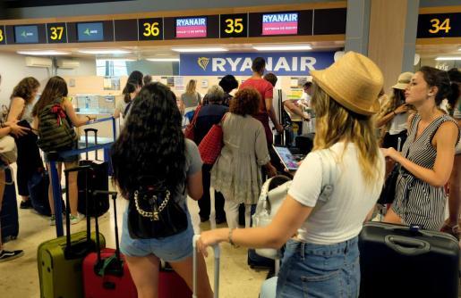 Un grupo de turistas hacen cola frente a una oficina de facturación de Ryanair.