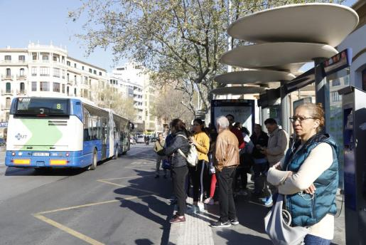 Usuarios de la EMT esperan en la parada del autobús.