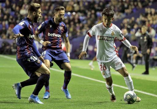 El centrocampista japonés del Mallorca, Takefusa Kubo (d), intenta llevarse el balón ante los jugadores del Levante, José Luis Morales (c) y Rubén Rochina, durante el encuentro correspondiente a la jornada catorce de primera división disputado esta noche en el estadio Ciutat de Valencia.