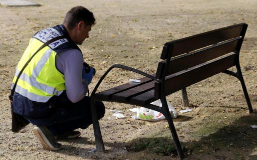 Un agente de la Policía Científica, recogiendo pruebas en el lugar donde se produjo la agresión.