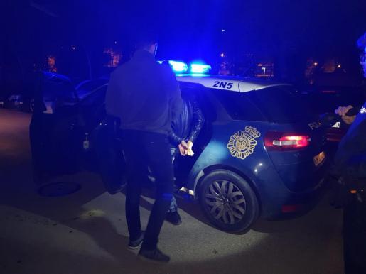 Momento en el que uno de los detenidos es introducido en el coche policial.