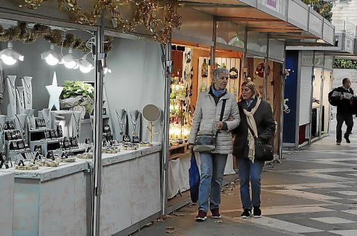 Dos personas pasean por el mercado de artesanía de la Rambla.
