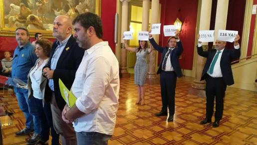 Imagen coincidente con un anterior pleno en el Parlament. A la izquierda los representantes de Més comparecen ante los medios. Mientras, a la derecha, los diputados de Vox protestan con carteles.