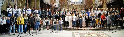 Grupo de los 140 alumnos del Colegio Sueco, de Palma, ayer al mediodía, en el altar mayor de la Catedral de Palma, durante el ensayo de la celebración de Santa Lucía.