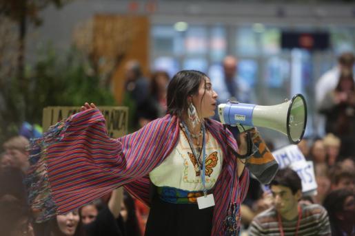 """Una activista del movimiento Fridays for Future habla a través de un megáfono durante una sentada en el pabellón 4 en protesta por los resultados """"insuficientes"""" logrados en la Cumbre del Clima."""