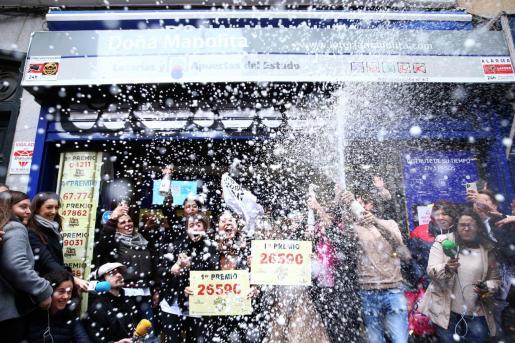 Un grupo de personas celebran en la administración madrileña de Doña Manolita que ha vendido el número 26.590, agraciado con el Gordo de Navidad.