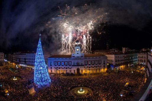 El reloj de la Puerta del Sol da las campanadas de fin de año, frente a la mirada de miles de personas que se reúnen hoy en Madrid (España), mientras otros siguen la transmisión de televisión y comen las tradicionales doce uvas.