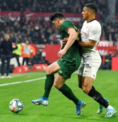El defensa brasileño Diego Carlos (d), del Sevilla FC, lucha con Ander Capa, del Athletic Club de Bilbao, durante el partido de la 19ª jornada de LaLiga que se juega hoy viernes en el estadio Ramón Sánchez-Pizjuán, en Sevilla.