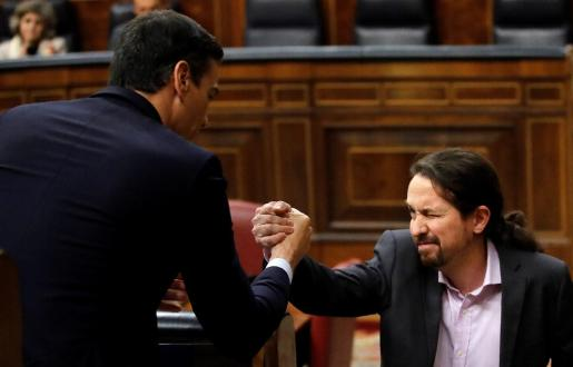 El líder de Unidas Podemos, Pablo Iglesias, saluda a Pedro Sánchez (i), tras su intervención ante el pleno del Congreso de los Diputados en la primera jornada de la sesión de investidura de Pedro Sánchez como presidente del Gobierno.