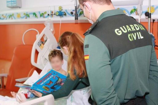 Un teniente de la Guardia Civil junto a dos niños en el hospital de Son Espases.