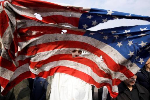 Un manifestante rompe una bandera estadounidense durante una manifestación multitudinaria contra EEUU, este viernes en Teherán (Irán), después de que el Pentágono reivindicase el bombardeo selectivo que acabó con la vida del comandante de la Fuerza Quds de los Guardianes de la Revolución de Irán, Qasem Soleimaní.