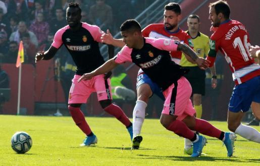 -El defensa del Granada Víctor Díaz (d), y el delantero colombiano del Mallorca Juan Camilo Hernández (c), durante el partido de la jornada 19 de LaLiga Santander que se disputó en el estadio Nuevo Los Cármenes de Granada.