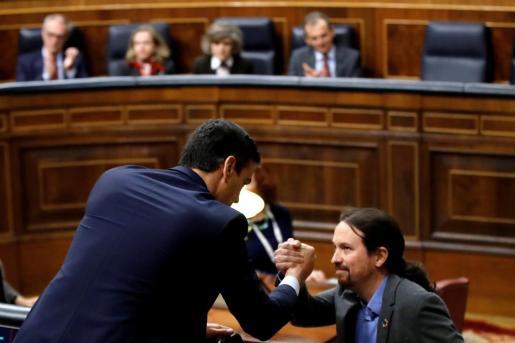 Los socios de Gobierno Pedro Sánchez y Pablo Iglesias se saludan.