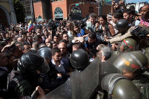 Diputados opositores, simpatizantes de la oposición y miembros de la prensa forcejean con efectivos de la Guardia Nacional Bolivariana (GNB) que custodian las entradas al Palacio Federal Legislativo en Caracas.