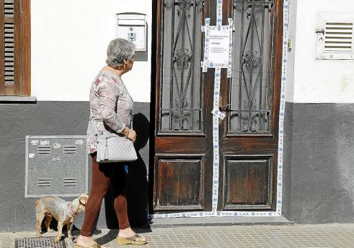 Una mujer pasea con un perro junto a la puerta de la planta baja donde ocurrió el crimen, en el Arenal.